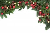 Christmas background floral border with bauble decorations, holly, ivy, mistletoe, pine cones and fir over white with copy space.