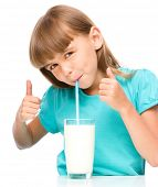 Cute little girl drinks milk and showing thumb up sign using both hands, isolated over white