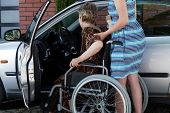 stock photo of independent woman  - Young woman helping a disabled lady get in the car - JPG