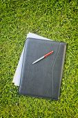 Documents In A Leather Folder Over Green Grass