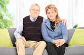 Lovely mature couple hugging seated on sofa at home