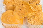 tortilla nachos chips with cheese sauce in plastic container on white background