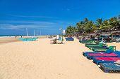HIKKADUWA, SRI LANKA - FEBRUARY 24, 2014: Wooden deck chairs on sandy beach. Hikkaduwa is well known tourist international destination for board surfing.