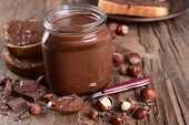 stock photo of chocolate spoon  - Sweet chocolate cream in jar on table close - JPG