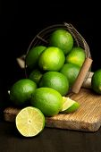 Fresh juicy limes in basket on wooden table, on dark background