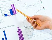 female hand pointing pencil on financial charts