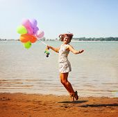 a pretty woman enjoying summer outside with a bunch of balloons
