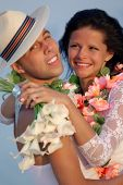Groom with bride wearing lei, standing under archway on beach (Focus is on bride)