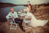 Groom next to table on the rock and excited bride hold fist ok yes gesture with raised arm