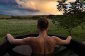 Bathing woman relaxing in outdoor bath or tub and watching sunset