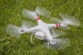 FORT COLLINS, CO, USA, AUGUST 1 2014:  Radio controlled DJI Phantom quadcopter drone taking off from a grass field