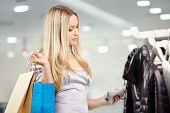 stock photo of clothes hanger  - Attractive happy blonde chooses clothes in shop - JPG