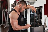 Bodybuilder Looking At His Phone