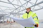 stock photo of engineering construction  - male engineer construction foreman manager outdoors indoors at building site with blueprints - JPG