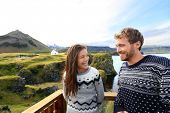 Tourist couple on romantic travel on Iceland. Happy couple sightseeing as tourists visiting landmarks and attractions in Arnarstapi, Snaefellsnes, Iceland.