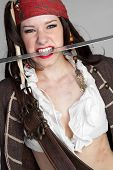 stock photo of wench  - Sexy angry pirate biting sword in teeth - JPG