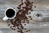 Dark Coffee And Beans On Rustic Wood
