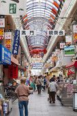 People Shopping In The Kuromon Market In Osaka, Japan