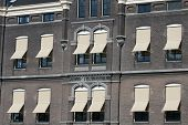 pic of awning  - Old building with creme awnings on a sunny day - JPG