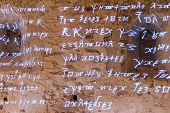 picture of rune  - Glowing antique runes characters and letters of words from glowing text of ancient writings on the rough stone wall - JPG