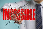 Businessman Hand Hitting Red Impossible Word On Cracked Transparent Glass