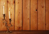 Retro candlestick with candles on wooden background