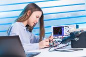 stock photo of circuit  - Girl repairing electronic device on the circuit board - JPG