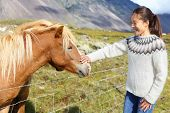 Horse - woman petting Icelandic horses in sweater on Iceland. Happy smiling girl going horseback riding.