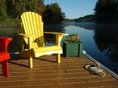 Muskoka Chairs and Flower Pot on the Dock at the Lake