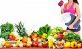 Woman with scales and dumbbell fruits and vegetables background