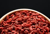 Wooden Bowl Full of Dried Goji Berries on the Black Table. Healthy Diet