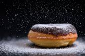 stock photo of donut  - Sprinkling sugar on delicious donut topped with chocolate - JPG