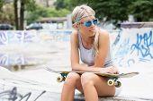 Girl with skateboard sitting in skatepark
