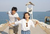 Young Man And Pretty Woman Joyful Emotion And Playing At Sea Side Vacation And Relaxing Time