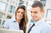 stock photo of office romance  - Portrait of a young business couple while standing in front of office building looking at laptop - JPG
