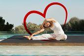 Peaceful brunette in janu sirsasana yoga pose poolside against heart