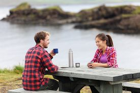 foto of camper  - Camping couple sitting at table drinking coffee from thermos bottle flask by lake on Iceland - JPG