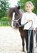 stock photo of pony  - little cute girl standing next to a pony in the stable - JPG