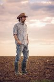pic of farm land  - Portrait of Adult Male Farmer Standing on Fertile Agricultural Farm Land SoilLooking into Distance - JPG
