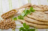 stock photo of chickpea  - Lebanese bread pita bread nice and fresh chickpeas in background simple cheap bread with herbs and garlic - JPG