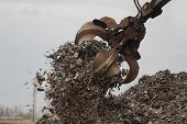 stock photo of polution  - Grabber crane at the car waste yard