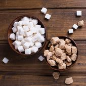 image of sugar cube  - White and brown sugar cubes in bowls on dark painted wooden planks - JPG