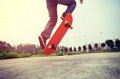 pic of skateboarding  - young skateboarder  legs doing skateboarding trick ollie outdoor - JPG