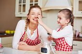 picture of lol  - Little girl smutching her mother face with flour in the kitchen - JPG
