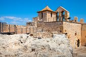 stock photo of yellow castle  - Small medieval stone castle on the rock in ancient Calafell town Spain - JPG