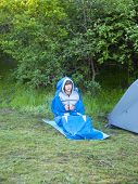 stock photo of sleeping bag  - The man is resting in a sleeping bag on the background of tents and green forests.