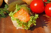stock photo of baguette  - Slice of baguette with smoked salmon filet garnished with lettuce onion tomato and pickles on a wooden board - JPG