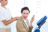 stock photo of unnerving  - Upset businesswoman having back massage in medical office - JPG