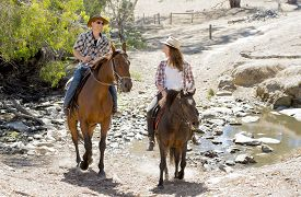 picture of cowgirl  - young American Australian man as father or horse instructor of young girl or teen daughter riding little pony wearing cowgirl hat in countryside Summer vacation ride - JPG