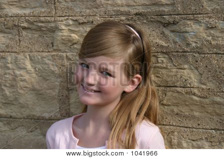 Picture or Photo of Pretty blonde preteen girl in pink smiling outdoors by stone wall